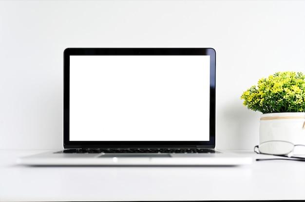 Leeg scherm moderne laptopcomputer met muis, slimme telefoon en sappig op houten tafel op kantoor achtergrond