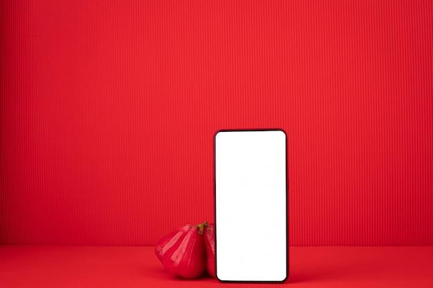Leeg scherm op mobiele telefoon met rose apple fruit op rode achtergrond.