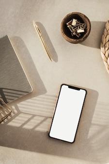 Leeg scherm slimme telefoon, briefpapier op beige achtergrond. gestileerde kantoor aan huis werkruimte.