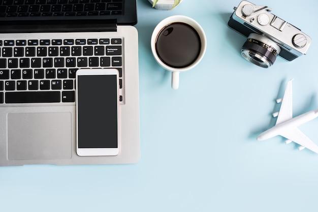 Leeg scherm slimme telefoon en computer met reisartikelen op gekleurde achtergrond met kopieerruimte, vakantieplanningsconcept