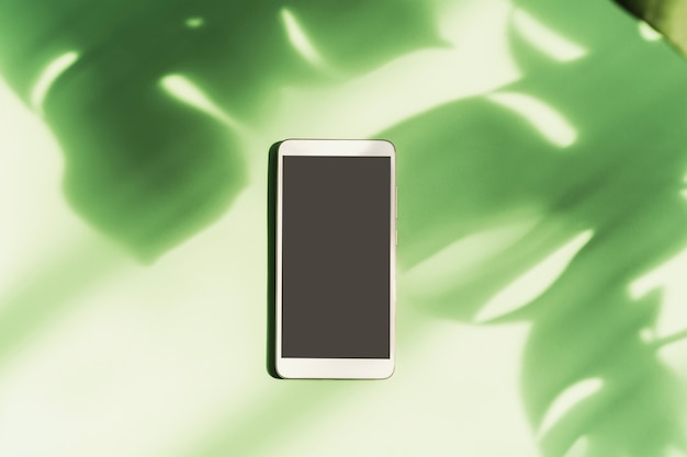Leeg scherm slimme telefoon met schaduw van tropisch groen verlof