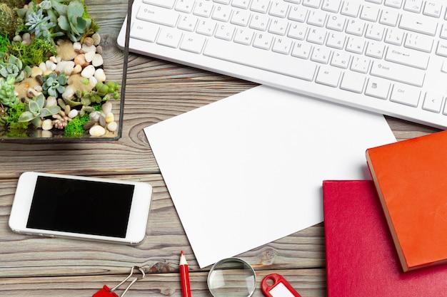 Leeg scherm smartphone voor copyspace en kantoorbenodigdheden op houten