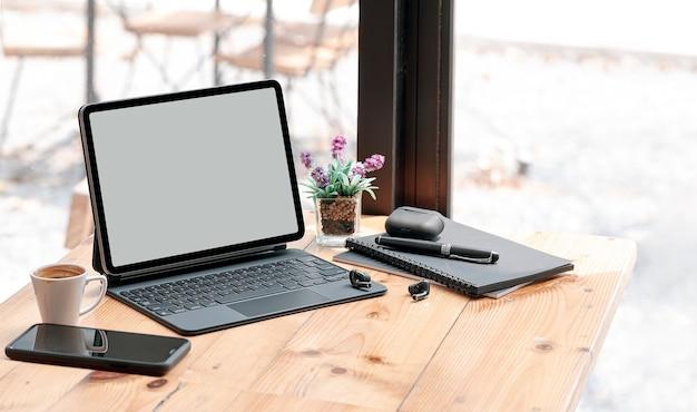 Leeg scherm tablet en gadget op houten aanrechttafel in café. Premium Foto