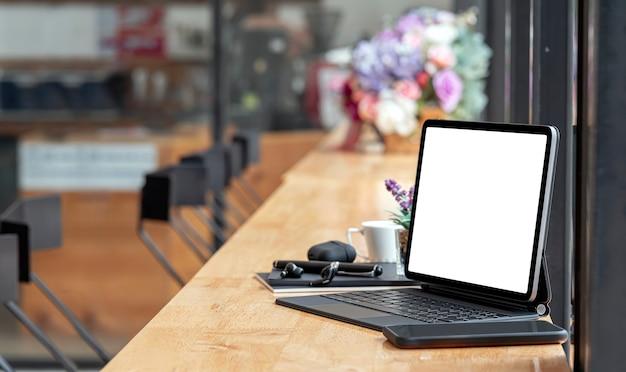 Leeg scherm tablet en gadget op houten aanrechttafel in café.
