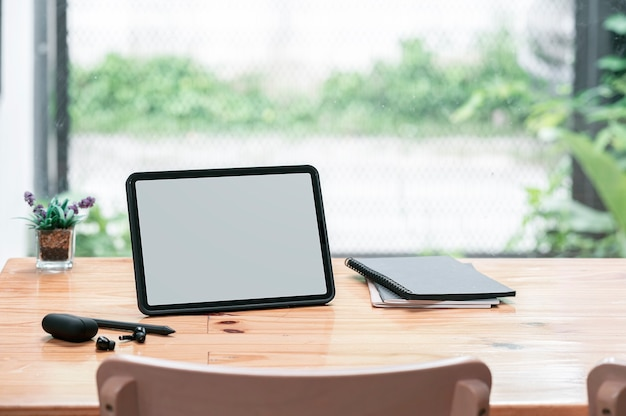 Leeg scherm tablet en notebook op houten tafel in café kamer.