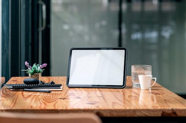Leeg scherm tablet, koffiekopje en gadget op houten tafel in café kamer.