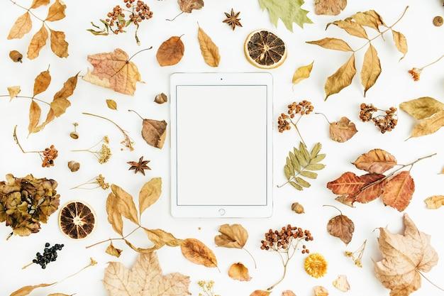 Leeg scherm tablet met droge herfst herfstbladeren, bloemblaadjes en sinaasappels op wit oppervlak