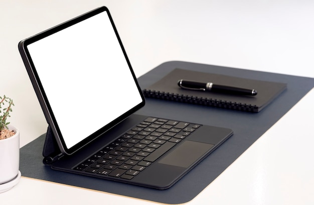 Leeg scherm tablet met toetsenbord, notebook en pen op witte tafel.