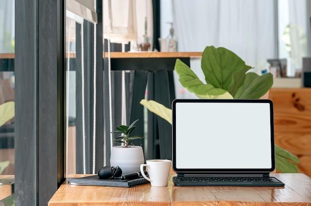 Leeg scherm tablet met toetsenbord op houten tafel in café.