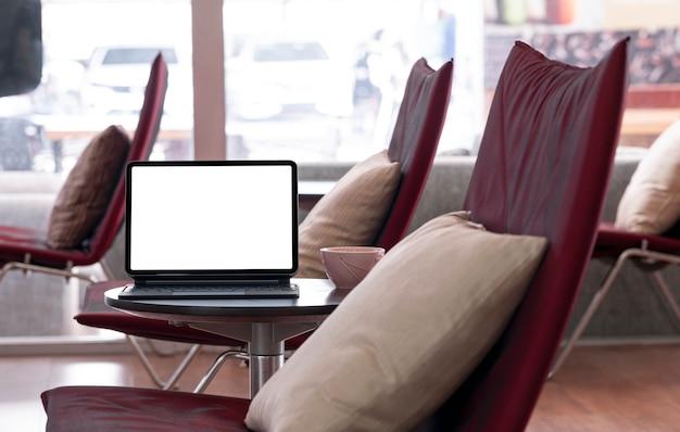 Leeg scherm tablet met toetsenbord op salontafel in de rustruimte.