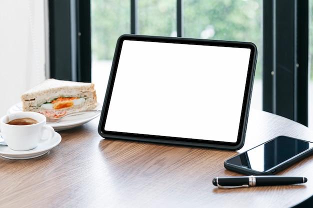 Leeg scherm tablet, smartphone en koffiekopje op houten tafel in café
