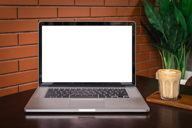 Leeg scherm van laptopcomputer met latte art koffie op tafel met bakstenen muur