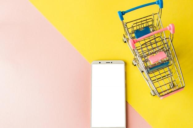 Leeg scherm witte mobiel en winkelwagentjes op pastel roze en geel. minimale stijl, flatlay