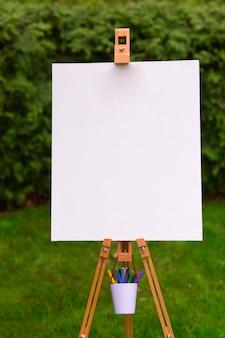 Leeg schildersezelmalplaatje op de tuinachtergrond