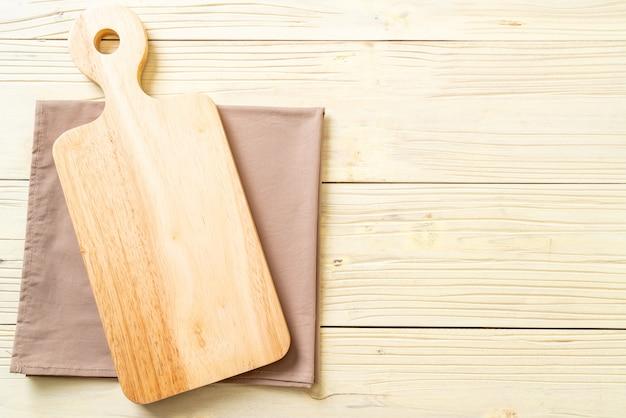 Leeg snijden houten bord met keuken doek achtergrond