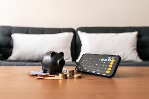 Leeg spaarvarken en de hoeveelheidhoeveelheid besparingen in een calculator. geld concept opslaan