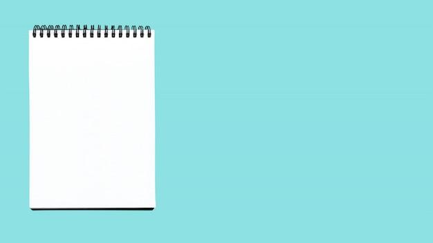 Leeg spiraalvormig die notitieboekje op blauw wordt geïsoleerd