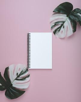 Leeg spiraalvormig notitieboekje en bladmonsters op pastelkleur