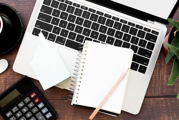 Leeg spiraalvormig notitieboekje met potlood over open laptop op houten lijst