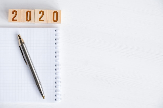 Leeg spiraalvormig notitieboekje, pen, houten kubussen met aantallen nieuw jaar
