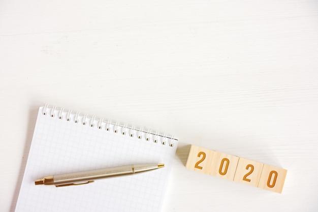 Leeg spiraalvormig notitieboekje, pen, kubussen met aantallen nieuw jaar