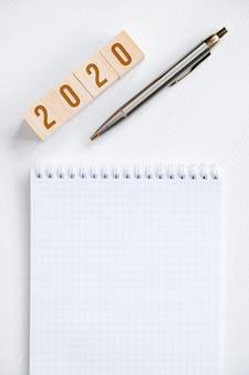 Leeg spiraalvormig notitieboekje, vulpen, houten kubussen met aantallen nieuw jaar