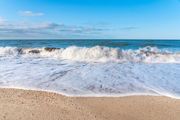 Leeg strand met geel zand en blauwe golven, quarantaine in het resort