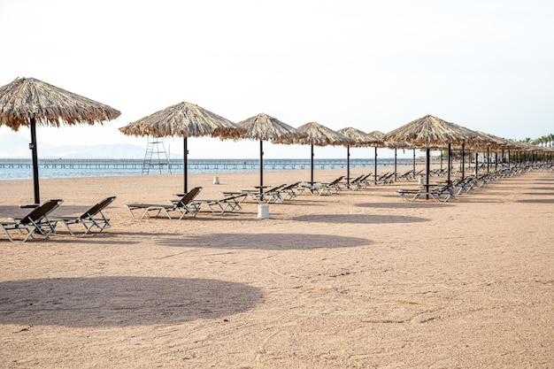 Leeg strand met ligstoelen en parasols. toeristencrisis tijdens quarantaine.