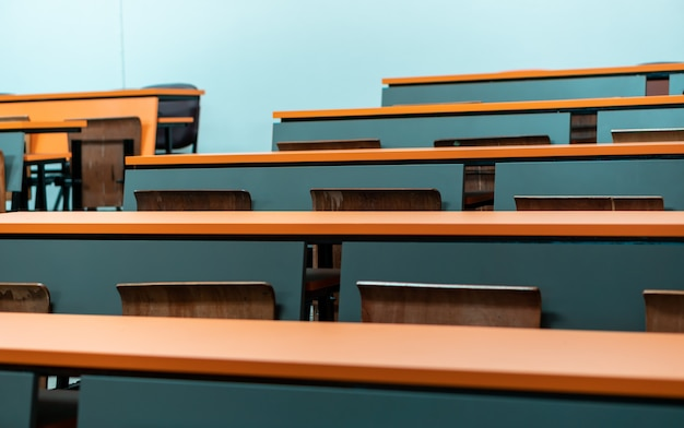 Leeg studentenbureau met houten stoel in het lezingsklaslokaal van universiteit