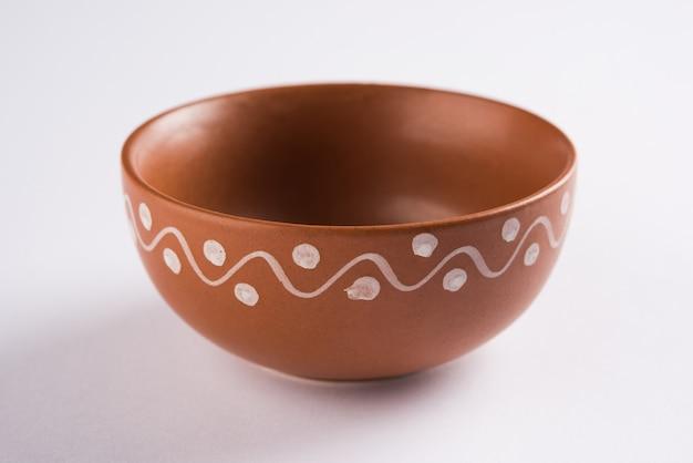 Leeg terracotta servies of eetset zoals bord, soepkom, serveerschaal, glas gemaakt van bruine klei, geïsoleerd over wit