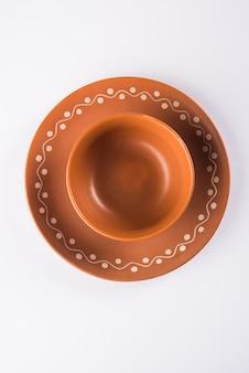 Leeg terracotta servies of eetset zoals bord, soepkom, serveerschaal, glas gemaakt van bruine klei, geïsoleerd over wit Premium Foto