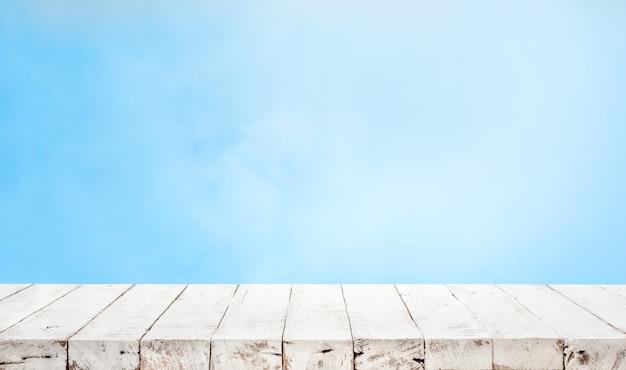 Leeg van houten tafelblad op blauwe pastel kleur achtergrond.