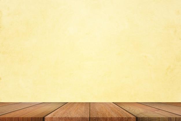 Leeg van houten tafelblad op lichtgele pastel kleuren achtergrond.
