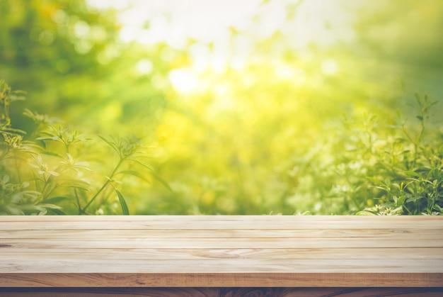 Leeg van houten tafelblad op vervaging van verse groene samenvatting van tuin achtergronden