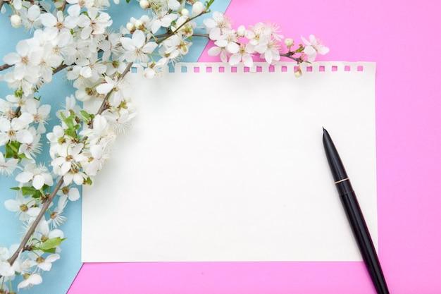 Leeg vel notitieblok met pen op een roze-blauwe achtergrond met bloesem bloemen. kopieer ruimte voor lentetekst.