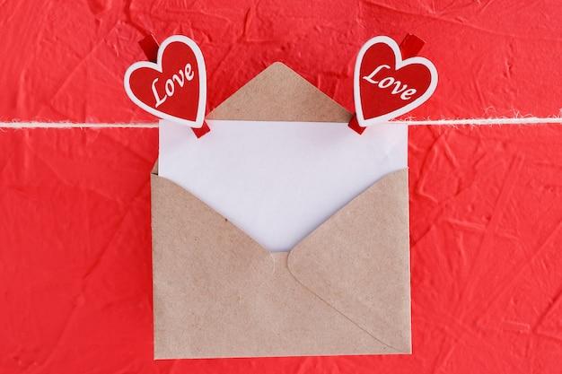 Leeg vel papier in envelop hangt aan een touw bevestigd met hartvormige wasknijpers op een rood voor valentijnsdag