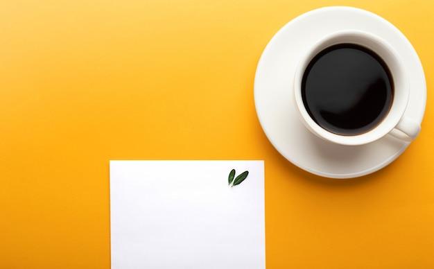 Leeg vel papier kladblok en een kopje koffie op een gele achtergrond met kopie ruimte. planning concept, ochtend, lijst.