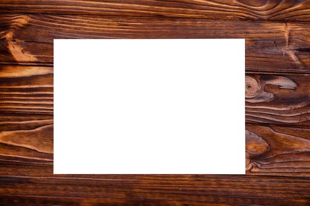Leeg vel papier op een houten achtergrond. flatfly