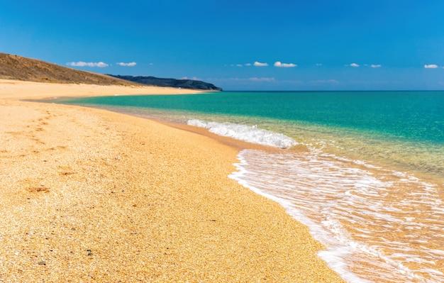 Leeg verlaten strand met schelpzand en kristalheldere zee