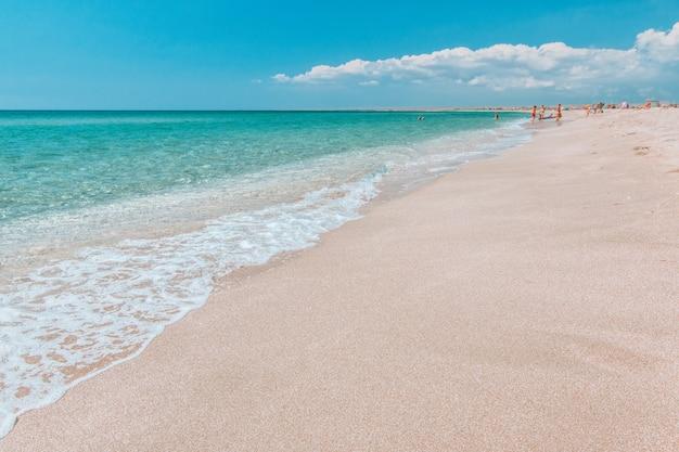Leeg verlaten strand met wit zand en kristalheldere azuurblauwe zee