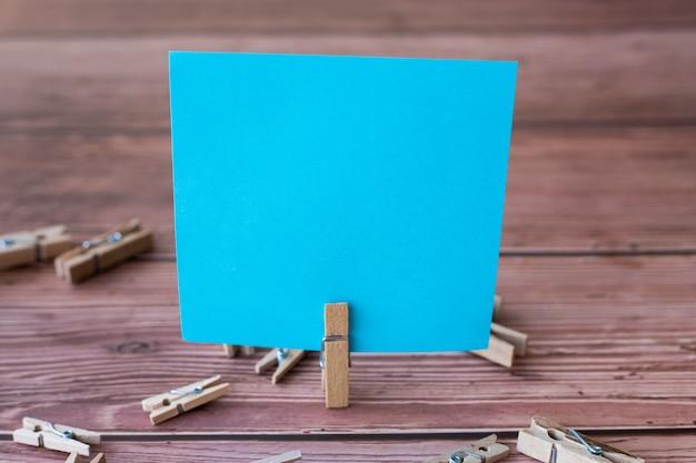 Leeg vierkant briefje omringd door wasclips met een nieuwe betekenis leeg stuk plakkerig papier