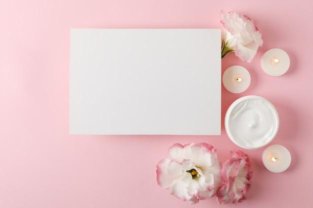 Leeg vierkant, kaarsen, bloemen en room op roze achtergrond, ruimte voor tekst