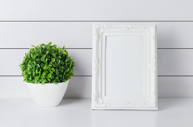 Leeg vintage fotoframe met groene huis plant