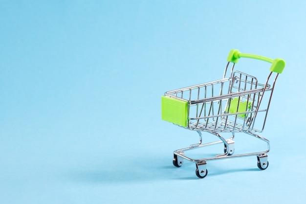 Leeg winkelwagentje op blauwe ruimte, mini metalen trolley geïsoleerd op gekleurde ruimte met plaats voor tekst.