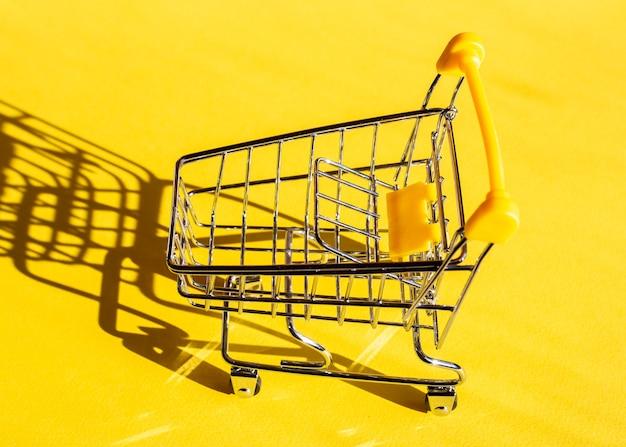 Leeg winkelwagentje op een heldere verfrissende gele achtergrond. kleuren van het jaar. winkelconcept.