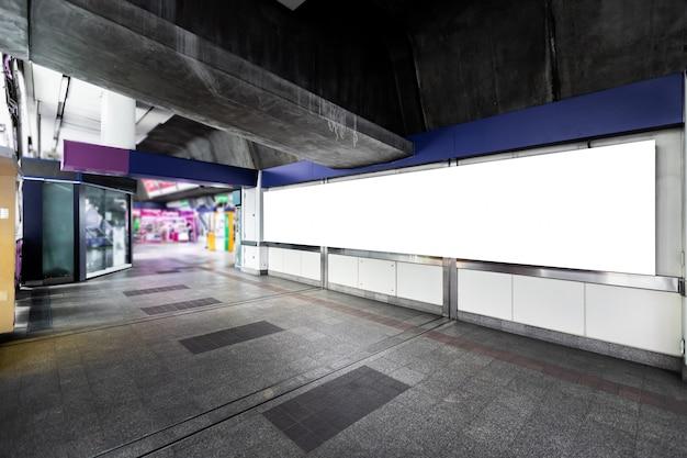 Leeg wit aanplakbord klaar voor nieuwe reclame voor klantinformatiediensten in openlucht bij skytrainstation