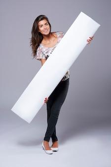 Leeg wit bordje gedragen door een jonge vrouw