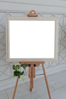 Leeg wit fotoframe op schildersezel