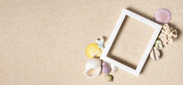 Leeg wit fotolijstje en meng zeeschelpen met koralen op schoon wit zand, bovenaanzicht, kopieer ruimte