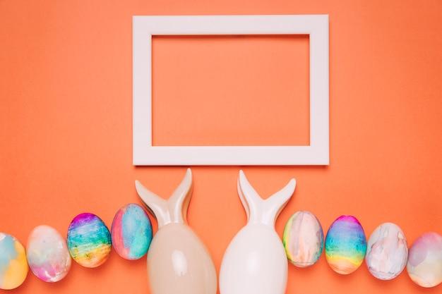 Leeg wit frame dat met kleurrijke paaseieren op een oranje achtergrond wordt verfraaid